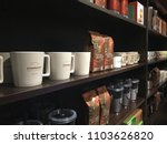 Small photo of KUWAIT CITY, KUWAIT - May 2, 2018 : Display shelf containing coffee products and merchandise available for purchase at Starbucks coffee shop, one of the famous coffee shop in the world.