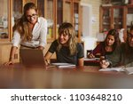 happy teacher helping her... | Shutterstock . vector #1103648210