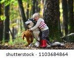 little girl embracing husky dog ... | Shutterstock . vector #1103684864
