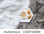 Stock photo cozy breakfast in bed cup of coffee and croissants on white and 1103723306