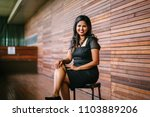 Small photo of Portrait of a confident, successful and attractive Indian Asian business woman sitting on a chair in a corridor of her office in the day. She is smiling for her professional head shot for Linkedin.