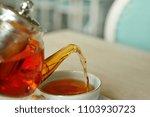 teapot pouring tea in cup | Shutterstock . vector #1103930723