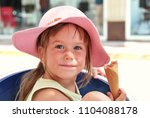 small girl with hat eat ice... | Shutterstock . vector #1104088178