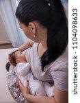 mother breastfeeding baby on... | Shutterstock . vector #1104098633