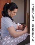 mother breastfeeding baby on... | Shutterstock . vector #1104098636