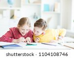 Small photo of Curious schoolboy looking at something in his classmate copybook and making fun of it
