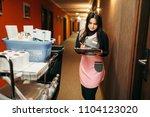 housemaid in uniform makes... | Shutterstock . vector #1104123020