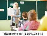 confident young teacher showing ... | Shutterstock . vector #1104126548