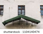 old house facade with green roof | Shutterstock . vector #1104140474