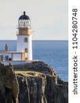 Small photo of The Neist Point lighthouse in side light taken by tele lens, Scotland, UK