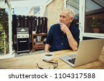 smiling senior man sitting at a ... | Shutterstock . vector #1104317588