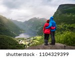 couple sitting on a rock with... | Shutterstock . vector #1104329399