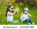 two little girls are drinking a ... | Shutterstock . vector #1104387488