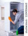 man cleaning fridge in hygiene...   Shutterstock . vector #1104506663