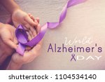 hands holding purple ribbons ... | Shutterstock . vector #1104534140