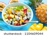 fruit salad in bowl on blue... | Shutterstock . vector #1104609044