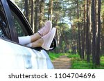 Small photo of Summertime, summer fun, enjoying, relaxing in the forest, lazy Sunday, tourism, travel, leisure time, vacation mode, happiness, forest road concept. Young woman's legs out of the car window.