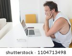 man with laptop on table at home | Shutterstock . vector #1104713498