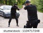 shootout between a police...   Shutterstock . vector #1104717248