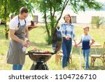happy family having barbecue... | Shutterstock . vector #1104726710