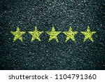 yellow five star on asphalt... | Shutterstock . vector #1104791360