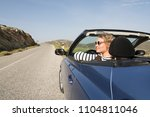 young blonde woman driving in... | Shutterstock . vector #1104811046