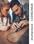 Small photo of Two young colleagues technician focused on the repair of electronic equipment.
