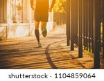 man running on road at sunset | Shutterstock . vector #1104859064