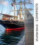 Small photo of Sydney, Australia - May 22, 2017: History on signboard. Restored Tall Ship James Craig (1874) moored to the pier, Sydney Heritage Fleet. At the Australian National Maritime Museum, Darling Harbor.
