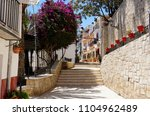 sunny street with flowers in... | Shutterstock . vector #1104962489