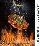 tasty beef steak flying above... | Shutterstock . vector #1105310159