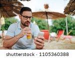 handsome man drinking orange... | Shutterstock . vector #1105360388