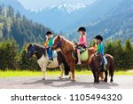 Stock photo kids riding pony in the alps mountains family spring vacation on horse ranch in austria tirol 1105494320