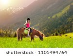 kids riding pony in the alps... | Shutterstock . vector #1105494764