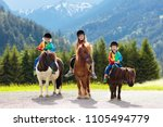 Stock photo kids riding pony in the alps mountains family spring vacation on horse ranch in austria tirol 1105494779