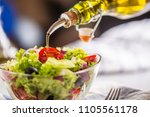 olive oil pouring in to bowl of ... | Shutterstock . vector #1105561178