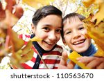Happy kid and autumn leaves in a park - stock photo