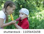 pretty little girl feeding a... | Shutterstock . vector #1105642658