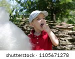 funny little boy eating cotton... | Shutterstock . vector #1105671278