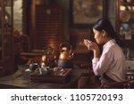 young asian girl drinking tea... | Shutterstock . vector #1105720193