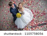 Stock photo newlyweds sprinkle with rose petals 1105758056