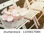 Stock photo basket with rose petals on the white chair on wedding close up copy space toned 1105817084