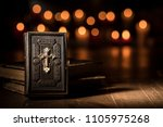 Small photo of Antique precious Bible and lit candles in the Church: religion and Catholicism concept