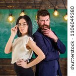 Small photo of Man with beard and teacher in eyeglasses stand back to back, chalkboard on background. Teacher and schoolmaster look confident. Teamwork concept. Lady and hipster working together in school.