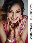 Small photo of Portrait of beautiful Hindu bride in pink sari getting sitting in a hotel room