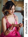 Small photo of Portrait of beautiful Hindu bride in pink sari getting ready for the ceremony in hotel room