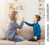 Small photo of Brother and sister playing clapping hands together at home. Children game, joint activities and interests, trust, support, entertainment concept