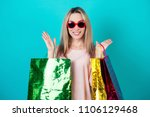 Small photo of portrait of a stylish and attractive crazy shopaholic woman in red sunglasses holding a lot of shopping bags surprised and shocked on a blue background in the studio. concept of shopaholism and sale