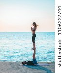Small photo of Young beautiful couple practicing acro yoga on the sea beach near water. Man and woman doing everyday practice outdoor on nature background. Healthy lifestyle concept.