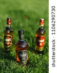 Small photo of bottles of grant's Scotch whiskey of different blend on green grass.